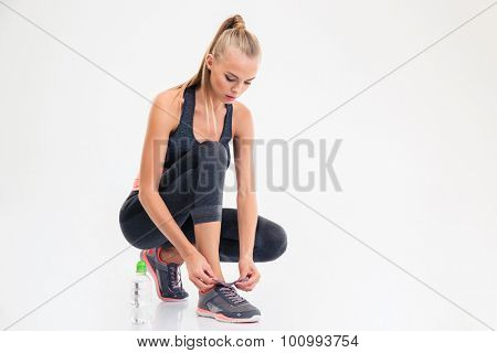 Portrait of a sports woman ties shoelaces isolated on a white background