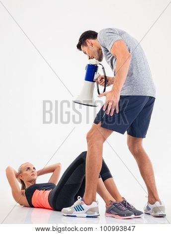 Concept photo of a male trainer shouting through megaphone on a sports woman to doing exercises isolated on a white background
