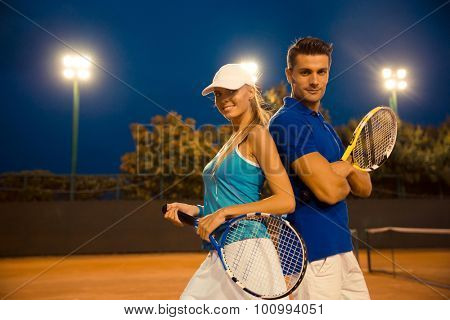 Couple of tennis players standing at the court