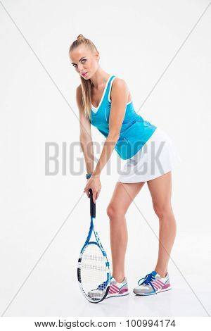 Full length portrait of a charming female tennis player standing isolated on a white background