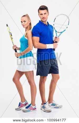 Full length portrait of a two tennis players standing isolated on a white background