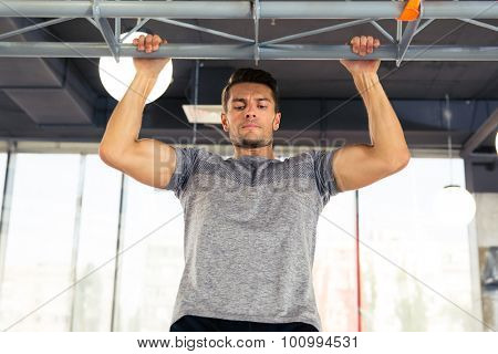 Portrait of a man tightening on horizontal bar at gym