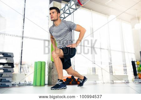 Portrait of a handsome fitness man doing warm-up exercises at gym