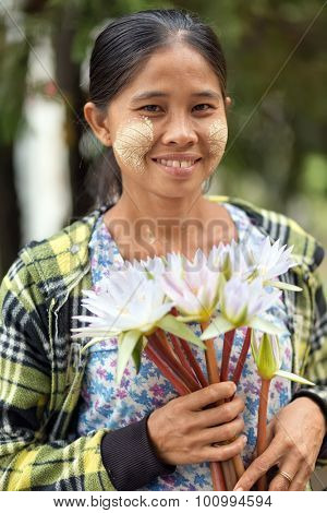 MANDALAY,MYANMAR,JANUARY 17, 2015 : Portrait of a woman with thanaka powder leaf patterns, selling waterlily flowers at the entrance of the pagoda Kuthodaw, in Mandalay, Myanmar (Burma).