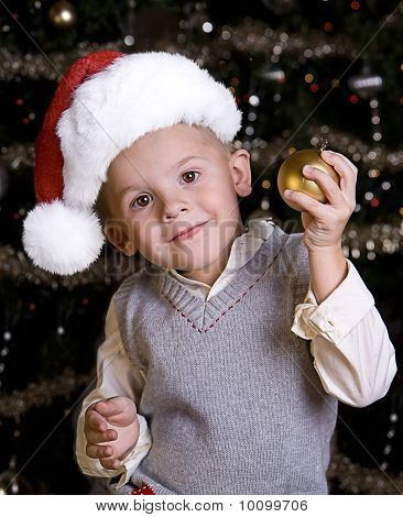Adorable Little Boy In A Santa Hat Holding An Ornament