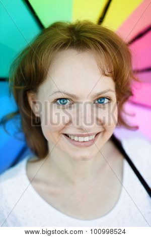 Girl Is Smiling Under Colorful Umbrella