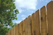 picture of wooden fence  - a wooden fence with a green tree and a cloudy sky - JPG