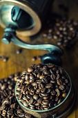 Постер, плакат: Roasted coffee beans spilled freely on a wooden table Coffee beans in a dish