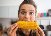 Постер, плакат: Teasing Happy Woman Taking Big Bite Of Corn On The Cob