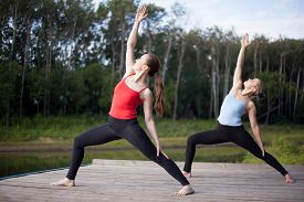 stock photo of virabhadrasana  - Two fit young beautiful women doing Reverse Warrior Pose Crescent lunge variation Viparita Virabhadrasana working out in park on summer day wearing sportswear red and blue tank tops full length - JPG