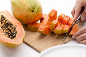 stock photo of papaya fruit  - Cutting a quarter of a papaya into six slices with a short kitchen knife - JPG