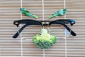 picture of cruciferous  - face of fresh broccoli with glasses on pattern bamboo for background - JPG
