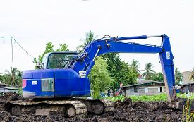 picture of backhoe  - Blue backhoe at house construction work site - JPG