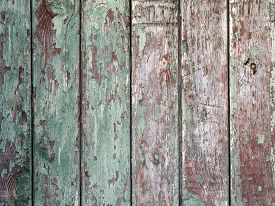 stock photo of wooden fence  - Detail of an old vertical wooden fence with the remains of green paint on the mangy dark boards with cracks for use as background or wallpaper - JPG
