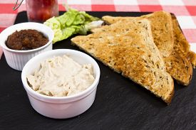 picture of canard  - a pot of creamy salmon pate on slate plate with pickle and triangles of toast - JPG