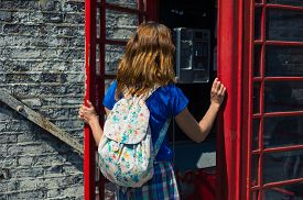 foto of phone-booth  - A young woman is entering a traditional red english phone booth on a sunny day - JPG