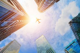 picture of high-rise  - Airplane flying over business skyscrapers - JPG