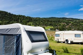 image of caravan  - Modern caravan with caravan tent at campsite in Norway on a sunny summer day - JPG