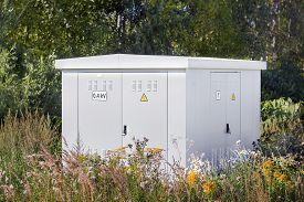 foto of transformer  - Electric power transformer in a meadow in summer - JPG