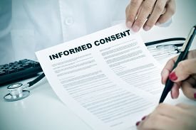 image of gynecological exam  - closeup of a young woman patient signing an informed consent at the doctors office - JPG
