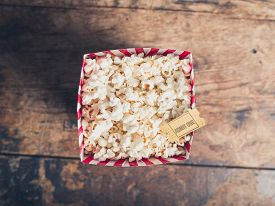stock photo of matinee  - Cinema concept of popcorn and movie ticket on a wooden table - JPG