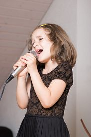 stock photo of karaoke  - Little cute girl singing karaoke on microphone at home - JPG