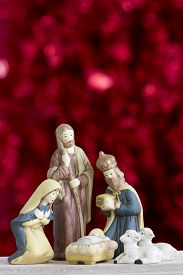 stock photo of baby sheep  - Nativity Scene with Baby Jesus Mary Joseph Sheep and a Wise Man on a Red Background with Copy Space Vertical - JPG