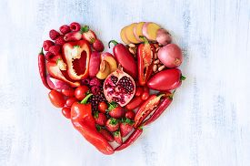 picture of pomegranate  - Collection of fresh red vegetables and fruits arranged in a heart shape on white rustic background strawberry raspberry pomegranate peppers capsicum chilli potato beans legumes - JPG