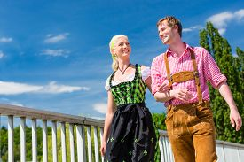 image of national costume  - Couple visiting together Bavarian fair in national costume leather pants and Dirndl  - JPG