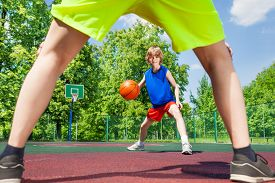 foto of legs apart  - View between two legs of player of boy with ball during basketball game on the playground outside - JPG
