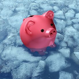 picture of freezing  - Frozen asset and budget freeze business concept or freezing wages financial symbol as a piggybank or piggy bank in ice and sinking in cold arctic water as a finance icon for not being able to sell an investent or redeem a fund - JPG