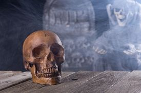 image of tombstone  - Spooky halloween human skull with grim reaper and tombstone in background - JPG