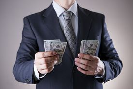 image of corruption  - Businessman with money in studio on a gray background - JPG