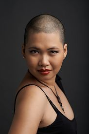 stock photo of shaved head  - Portrait of beautiful Vietnamese woman with shaved hair looking at the camera - JPG