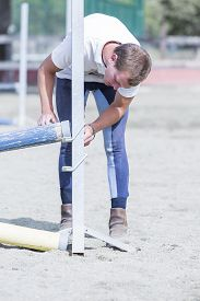 stock photo of horse-riders  - young horse rider placing jumping poles on a horse jumping session  - JPG