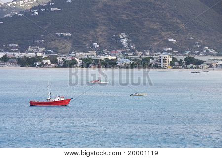 Red Fishing Boat Anchored In Tropical Bay