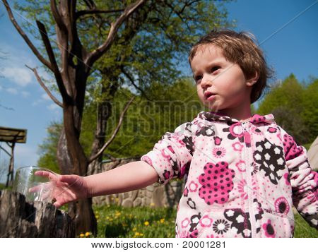 Small Girl Outdoors, With A Glass Of Water