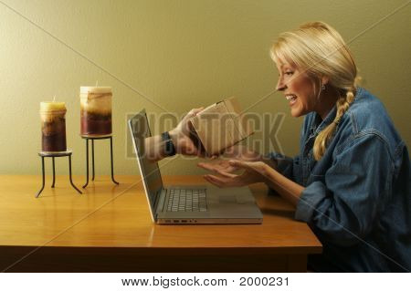 Hand & Package Coming Through Laptop Screen Toward Woman