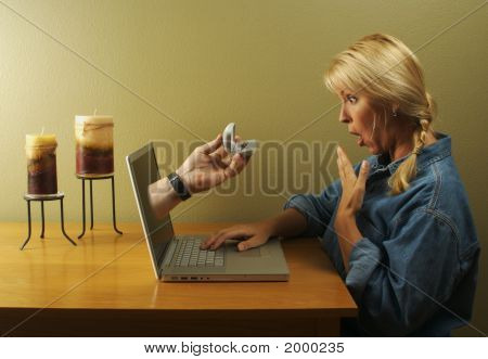 Hand & Ring Coming Through Laptop Screen Toward Woman.