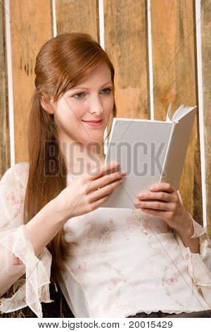Young Romantic Woman In Barn Reading Book