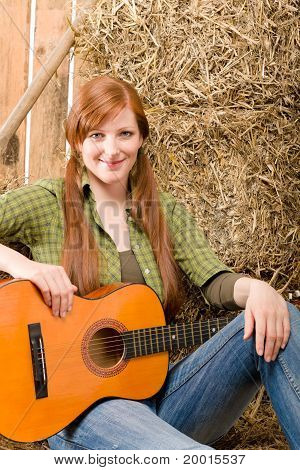 Young Country Woman Sitting On Hay With Guitar