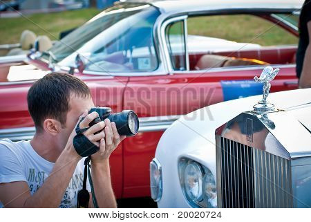 Photographer and retro car Rolls-Royceon exhibition parking