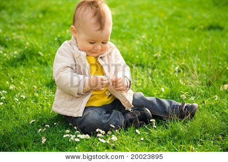 Little Boy Is Sitting On Green Meadow