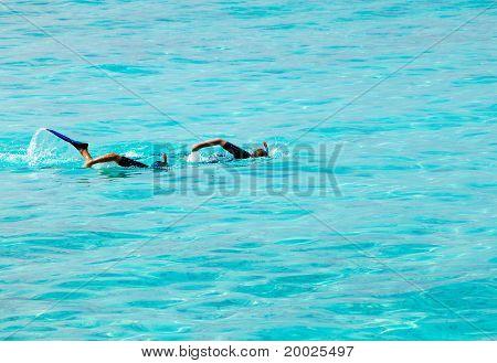 Zwei Männer mit Masken und Schläuchen Schwimmen synchron am Ozean