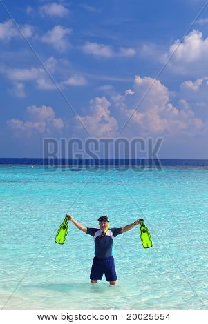 Young sports man with flippers mask and tube at ocean.Maldives.