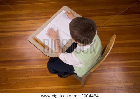 Boy Writting At School Desk