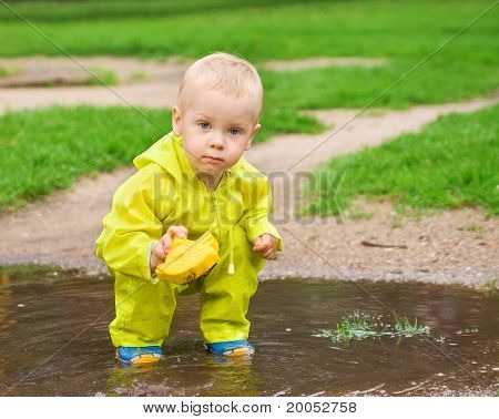 Child Playing With Ship In The Puddle Outdoor
