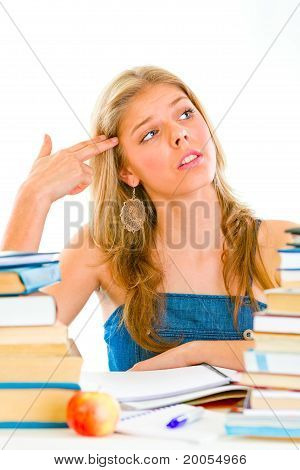 Stressful young girl sitting at table with books and holding gun shaped hand near head