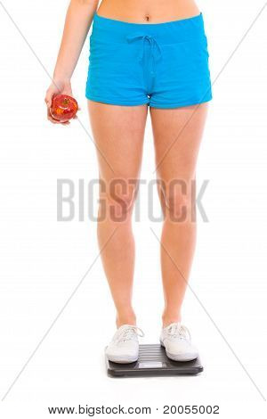 Girl standing on weight scales and holding apple in hand isolated on white. Close-up.