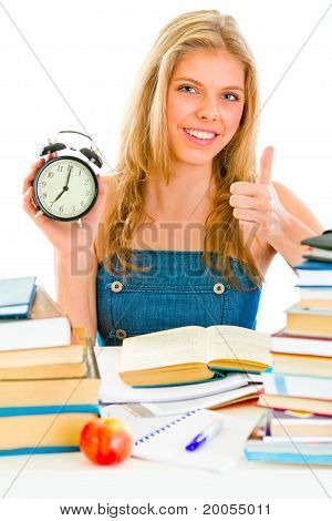Smiling teen girl with alarm clock sitting at table and showing thumbs up gesture